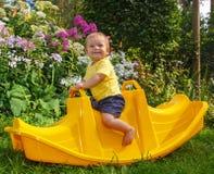 Weinig grappige baby op zijn favoriete schommeling Stock Fotografie