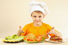 Weinig grappige chef-kok bij de lijst met ingrediënten voor hamburger Stock Fotografie