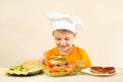 Weinig grappige chef-kok die in chef-kokshoed hamburger voorbereiden Royalty-vrije Stock Fotografie