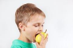 Weinig grappige jongen die in groen overhemd een gele peer eten Stock Foto's