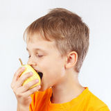 Weinig grappige jongen die in oranje overhemd een rijpe gele peer eten Royalty-vrije Stock Fotografie
