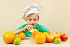 Weinig grappige jongen die verse sinaasappel pellen bij lijst met vruchten Royalty-vrije Stock Foto