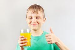Weinig grappige jongen met een glas vers jus d'orange Stock Afbeeldingen