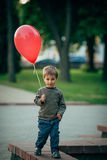 Weinig grappige jongen met rode ballon Stock Fotografie