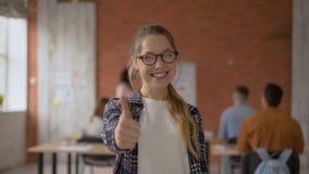 Weinig grappige studentenmeisje het lachen pret en het tonen beduimelt omhoog De student op de achtergrond van het publiek studen stock videobeelden
