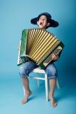 Weinig harmonikaspeler op blauwe achtergrond Stock Foto's