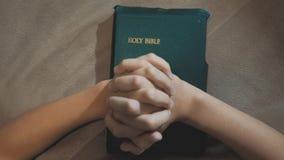 weinig heilige bijbel van het levensstijlmeisje bidt met bijbel in haar handen de katholicisme heilige heilige bijbel Kinderen en stock videobeelden