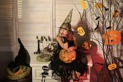 Weinig heks met Halloween-decor Meisje met verdacht gezicht stock afbeeldingen