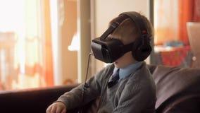 Weinig helm van de de werkelijkheidshoofdtelefoon van het jongensgebruik virtuele, maakte hij zeer op indruk stock video