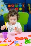 Weinig het kind van het babymeisje het spelen plasticine op de lijst Stock Fotografie