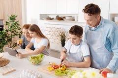Weinig het positieve jongen koken met zijn vader stock foto's