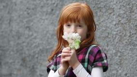 Weinig het roodharige meisje snuiven tot bloei komende tak stock videobeelden