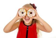 Weinig het vrouwelijke kind gelukkige spelen met suiker twee donuts als haar ogen stock fotografie