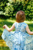 Weinig het wervelen meisje in een blauwe kleding in de zomertuin Stock Foto