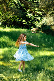Weinig het wervelen meisje in een blauwe kleding in de zomertuin Stock Fotografie