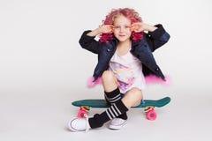 Weinig hipstermeisje met het gekleurde krullende kapsel met een skateboard rijden Ombre, gradiënt Royalty-vrije Stock Foto