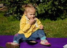 Weinig hongerige meisjeszitting op een gras en het eten van groene erwten royalty-vrije stock fotografie