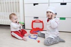 Weinig 4 jaar broer en 10 maanden zuster speelt arts Stock Foto's