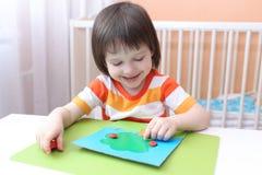 Weinig 3 jaar jongen van de modelleringsappel de boom van playdough Royalty-vrije Stock Afbeeldingen