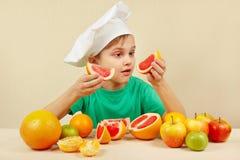 Weinig jong geitje in chef-kokshoed met twee plakken van grapefruit bij lijst met vruchten Royalty-vrije Stock Foto's