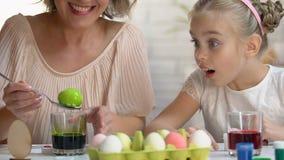 Weinig jong geitje die excitedly mamma het sterven op ei in groene voedselkleuring letten, Pasen-decor stock video