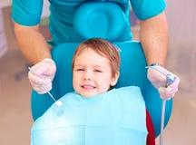 Weinig jong geitje, geduldige bang van tandarts terwijl het bezoeken van tandkliniek stock foto's