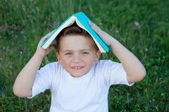 Weinig jong geitje het spelen met een boek bij buitenkant Stock Foto