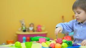 Weinig jong geitje het spelen met plastic speelgoed in kinderen` s ruimte stock footage