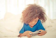 Weinig jong geitje het spelen met smartphone op bed Royalty-vrije Stock Afbeeldingen