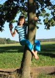 Weinig jong geitje - meisje het hangen op boomstam royalty-vrije stock foto