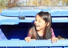 Weinig jong geitje - meisje het verbergen in een container Stock Fotografie