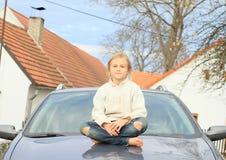 Weinig jong geitje - meisje op kap van auto stock afbeelding