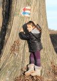 Weinig jong geitje - meisje wat betreft een boomstam Royalty-vrije Stock Foto