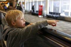 Weinig Jong geitje op Rollend trottoir die bij Luchthaven op Venster wijzen royalty-vrije stock afbeeldingen