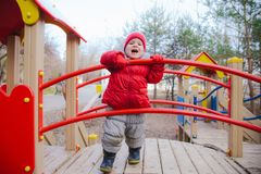 Weinig jong geitje speelt op de speelplaats in het park Stock Foto's