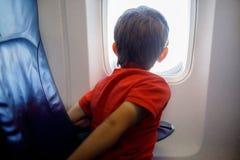 Weinig jong geitjejongen die buiten vliegtuigvenster tijdens vlucht op vliegtuig kijken royalty-vrije stock fotografie