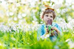 Weinig jong geitjejongen die chocoladepaashaas in openlucht eten Stock Fotografie