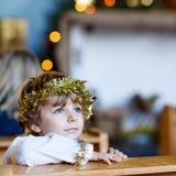 Weinig jong geitjejongen die een engel van Kerstmisverhaal spelen in kerk Stock Foto's
