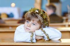Weinig jong geitjejongen die een engel van Kerstmisverhaal spelen in kerk Royalty-vrije Stock Afbeeldingen