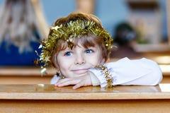 Weinig jong geitjejongen die een engel van Kerstmisverhaal spelen in kerk stock foto