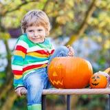 Weinig jong geitjejongen die hefboom-o-lantaarn maken voor Halloween in de herfstgeep Royalty-vrije Stock Fotografie