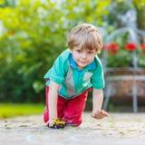 Weinig jong geitjejongen die met autostuk speelgoed spelen, in openlucht Stock Fotografie