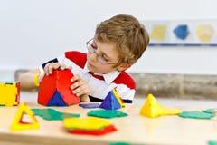 Weinig jong geitjejongen die met glazen met lolorful plastic elementenuitrusting spelen in school of peuterkinderdagverblijf Gelu stock afbeelding