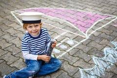 Weinig jong geitjejongen die pret met de tekening van het schipbeeld met krijt hebben Stock Afbeeldingen