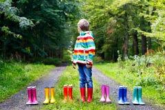Weinig jong geitjejongen en groep kleurrijke regenlaarzen Blond kind die zich in de herfst bosclose-up bevinden van schoolkind en stock afbeelding