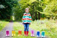 Weinig jong geitjejongen en groep kleurrijke regenlaarzen Blond kind die zich in de herfst bosclose-up bevinden van schoolkind en stock fotografie