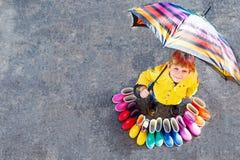 Weinig jong geitjejongen en groep kleurrijke regenlaarzen Blond kind die zich onder paraplu bevinden Close-up van schoolkind en royalty-vrije stock afbeelding