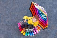 Weinig jong geitjejongen en groep kleurrijke regenlaarzen Blond kind die zich onder paraplu bevinden Close-up van schoolkind en stock foto