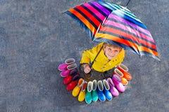 Weinig jong geitjejongen en groep kleurrijke regenlaarzen Blond kind die zich onder paraplu bevinden Close-up van schoolkind en stock afbeeldingen