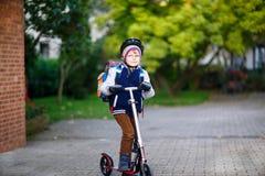 Weinig jong geitjejongen in helm het berijden met zijn autoped in de stad Stock Foto's